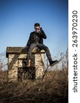 Small photo of Disheveled charismatic young man in black colored outfit, with roguish expression, sitting on abandoned concrete block of installation with pure blue sky in background and withered vegetation around.