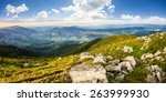 mountain panorama landscape. valley with stones in grass on top of the hillside of mountain range in dappled light - stock photo
