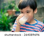 Little boy drinking milk in the ...
