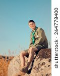 Small photo of Handsome Young Boy Scout Sitting on the Big Rock at the Field on a Sunny Day While Smiling at the Camera.