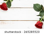 Two Red Roses On White Wooden...