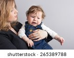 Small photo of The child is crying on the mother's arms.Portrait of mother and son. maudlin child