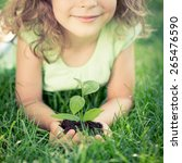 child holding young green plant ... | Shutterstock . vector #265476590