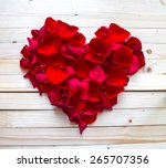 Stock photo heart made of red petals on wooden table 265707356