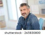smiling teacher sitting at desk ... | Shutterstock . vector #265830800