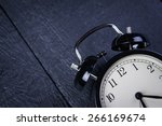 alarm clock on a black wooden... | Shutterstock . vector #266169674