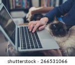 Stock photo a young woman is using her laptop at home with a cat sitting on her lap 266531066