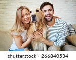 Stock photo happy young couple and their pet spending weekend at home 266840534