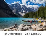 Rocky Mountain view at Moraine Lake in Banff National Park. Blue glacial water and fir trees with canoes.