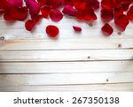 Stock photo rose petals border on a wooden table 267350138