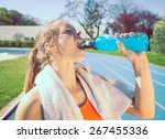 Stock photo woman drinking power drinking after long run concept about sport 267455336