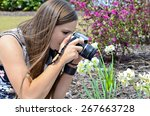 A teenager taking a photograph of her garden flowers. - stock photo
