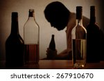 Small photo of silhouette of a person drinking behind bottles of alcohol with added filter
