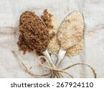 Small photo of Muscovado and demerara organic brown sugars on two silver spoons placed on a rustic linen tablecloth, close up. Landscape orientation.