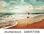 a woman jumping on the seashore | Shutterstock . vector #268457348