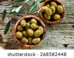 Small photo of Fresh olives and olive oil on rustic wooden background. Olives in olive wood.
