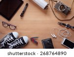 Overhead of essentials for modern young person. Different photography objects on wooden background: camera, smart phone, glasses, flashlight, digital tablet, wallet, watch, gumshoes, thermos - stock photo