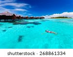 Young Woman Swimming From Hut...