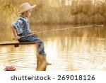 Little Boy Is Fishing At Sunset ...