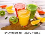 Small photo of Fresh juices with fruits on wooden table