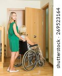 Small photo of woman in wheelchair with young assistant at threshold