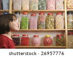 young girl smiling at camera in sweet shop - stock photo