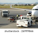 Loading suitcases and other cargo  in an airplane on the runway - stock photo