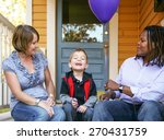 Small photo of a cute diverse family sitting on a porch