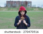 Small photo of portrait of a homeless boy holding a cardboard house