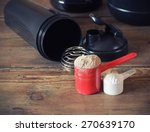 Stock photo whey protein powder in scoop with plastic shaker on wooden background 270639170