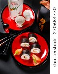 japanese maki sushi rolls set with salmon and avocado on red plate and sake - stock photo