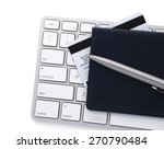 Small photo of Computer keyboard with a credit card and checkbook.