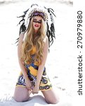 Small photo of Young blonde woman in costume of American Indian sits on the sand