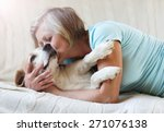 Stock photo senior woman with her dog on a couch inside of her house 271076138