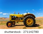 A Vintage Yellow Tractor Sits...