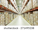 Small photo of interior of warehouse. Rows of shelves with boxes