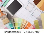 DIY and decorating work table with color swatches, paint brush, digital tablet and house project, top view - stock photo