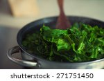 Vegetarian food concept. Fresh spinach cooking in metal pot. Close up. Indoor shot - stock photo