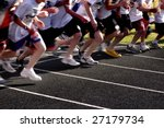 Runners running a race from the starting line - stock photo