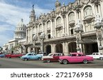 Row of brightly colored vintage American cars stand parked on the street in front of the Galician Palace on Prado Street in central Havana Cuba