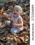baby girl showing autumn leaves | Shutterstock . vector #272206889