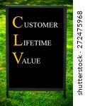 Small photo of Business Acronym CLV as CUSTOMER LIFETIME VALUE. Message on sidewalk blackboard sign against green grass background. Concept image