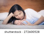 asian mother lays on her bed in ... | Shutterstock . vector #272600528