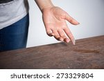 Small photo of Close-up of dust on woman finger taken from wooden table