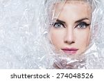 Small photo of Portrait of beautiful young woman, wrapped in cellophane