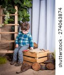 Small photo of Beautiful little boy is playing with the tools of a carpenter. Studio background of wood and burlap. Accustom the child to work from childhood