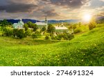 Composite image of green Monastery in mountains on hillside with grass and dandelions in sunset light - stock photo