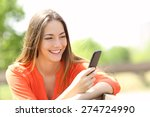 Happy girl using a smart phone in summer in a park