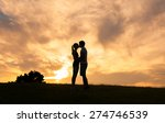 Couple Kissing At Sunset.