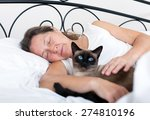 Stock photo beautiful older woman with cat sleeping on bed 274810196